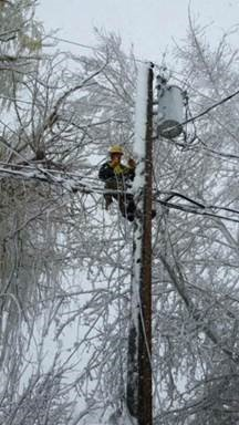 Lineworker on Power Pole in Ice Storm