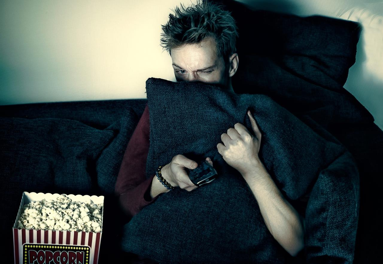 Man watching scary movie with popcorn