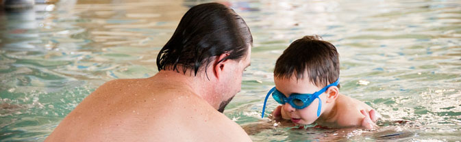 man assisting boy front glide swim lesson
