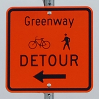 Greenway trail detour sign with arrow