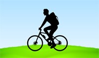 cyclist riding on green hill