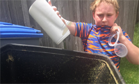 youngster putting compost into bin