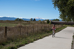 A woman rides a bicycle on a trail with mountains in the background