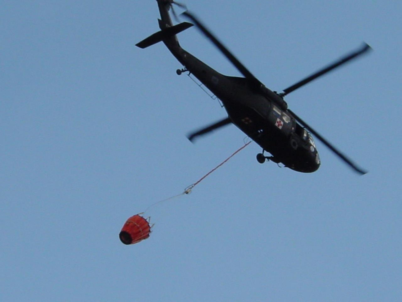 helicopter with bucket in air over Button Rock Preserve