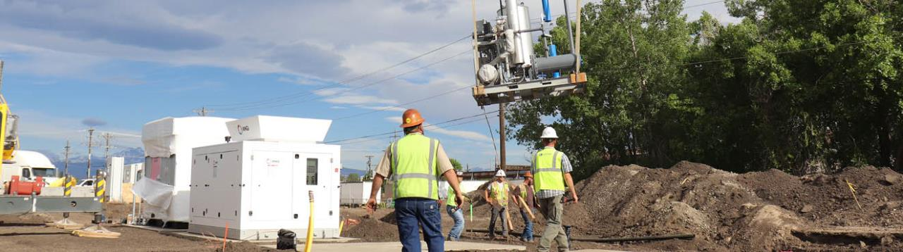 Workers wait for a part to be placed by a crane at the construction site of the Biogas facility