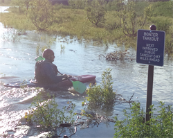 kayaker next to boating takeout sign in creek