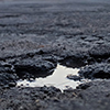 Pothole filled with some water on asphalt road