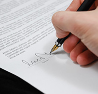 Person's hand holding a pen signing a document