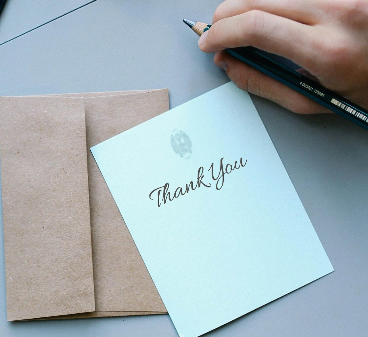 Thank You on Card with Envelope and Hand Holding Pen