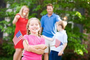 Girl with small US flags and family behind her